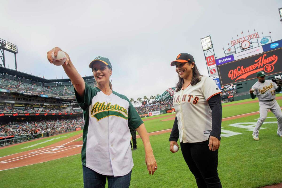 From left: Oakland Mayor Libby Schaaf and San Francisco Mayor London Breed practice their wind-up before simultaneously throwing out the first pitch before an MLB game between the San Francisco Giants and Oakland Athletics at Oracle Park, Friday, June 25, 2021, in San Francisco, Calif. It's the first game at the park without a capacity limit since the start of the coronavirus pandemic limited or banned spectators at sports venues.