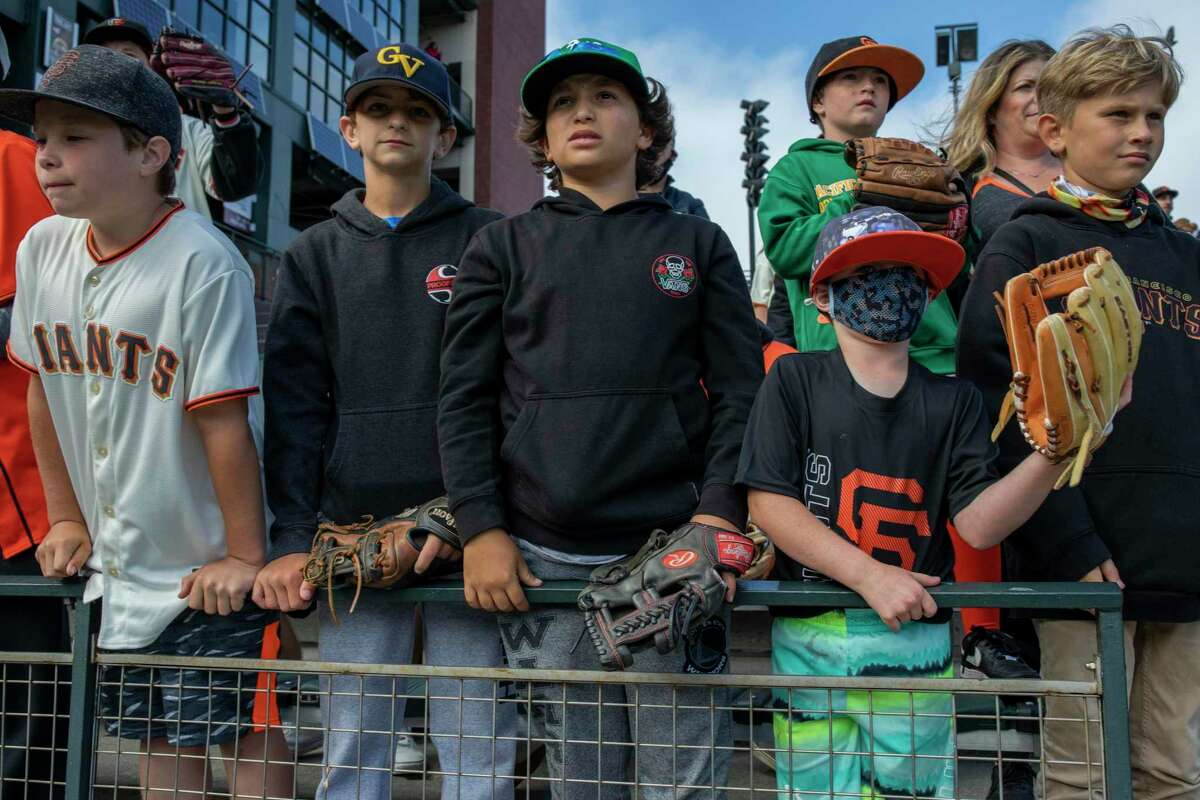 Children line up at Oracle Park to catch baseballs during batting practice before the San Francisco Giants take on the Oakland Athletics. Doctors say they are taking a number of precautions to keep their own kids safe in the face of the highly infectious delta variant of the coronavirus.