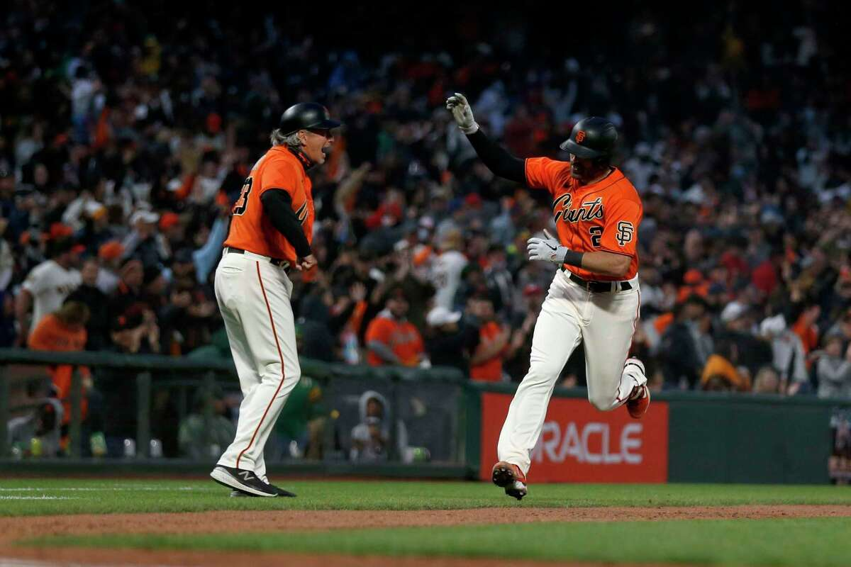 San Francisco Giants' Curt Casali, right, is congratulated by third base coach Ron Wotus after hitting a solo home run against the Oakland Athletics during the seventh inning of a baseball game in San Francisco, Friday, June 25, 2021. (AP Photo/Jed Jacobsohn)