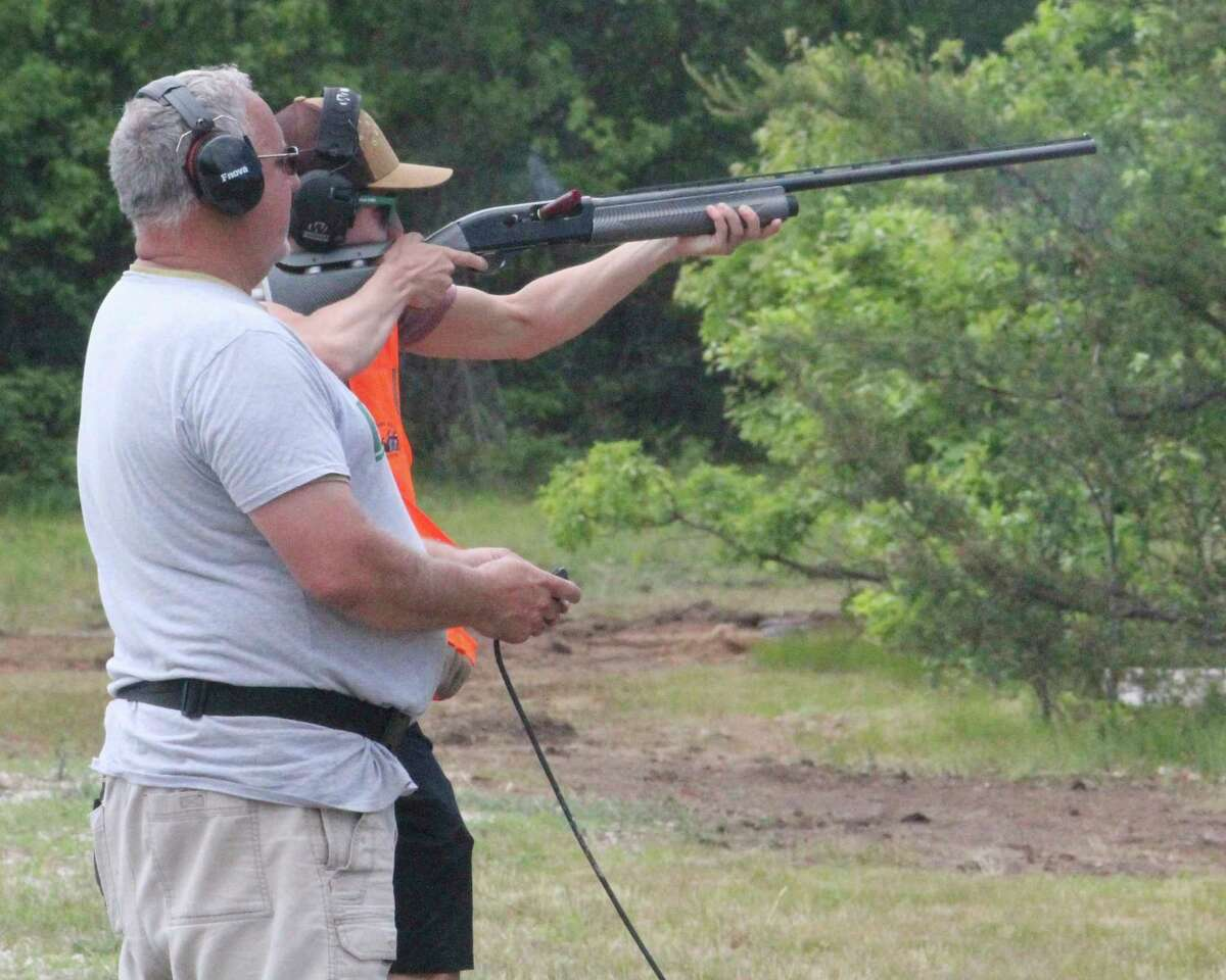 Doug Walls (left) of Baldwin watches as his son works out at the Lake County Sportsman Club trap field on Saturday. (Star photo/John Raffel)