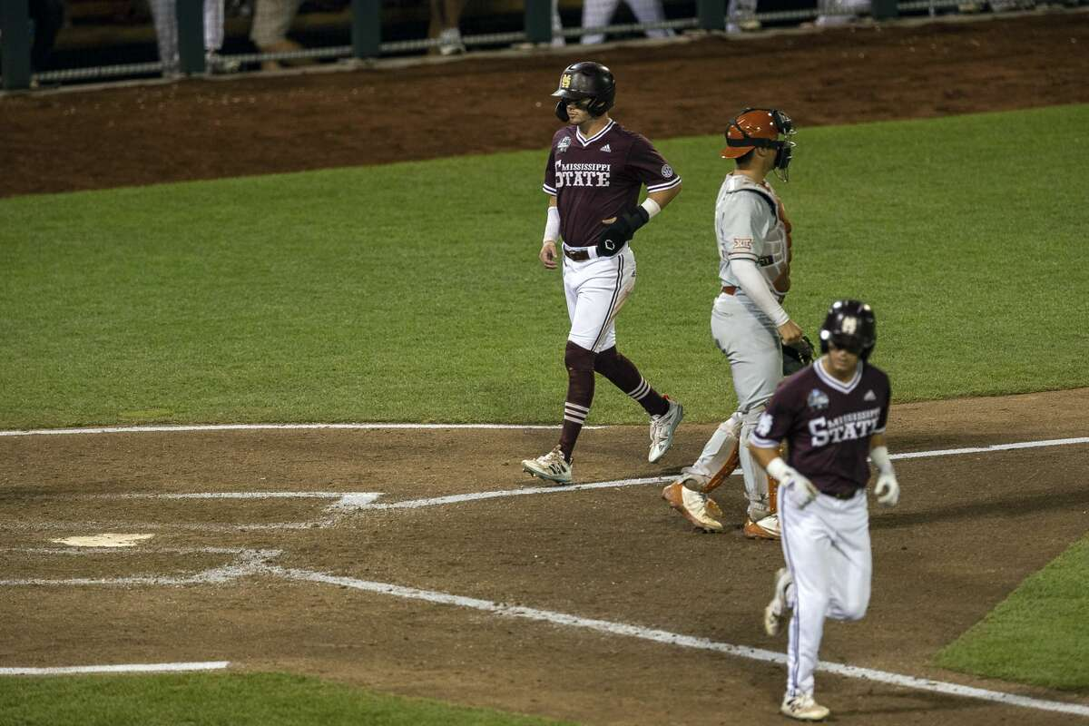 Mississippi State's Scott Dubrule (3) gets a walk from Texas's Tanner Witt (11) scoring Tanner Allen (5) during a baseball game in the College World Series Friday June 25, 2021, at TD Ameritrade Park in Omaha, Neb. (AP Photo/John Peterson)