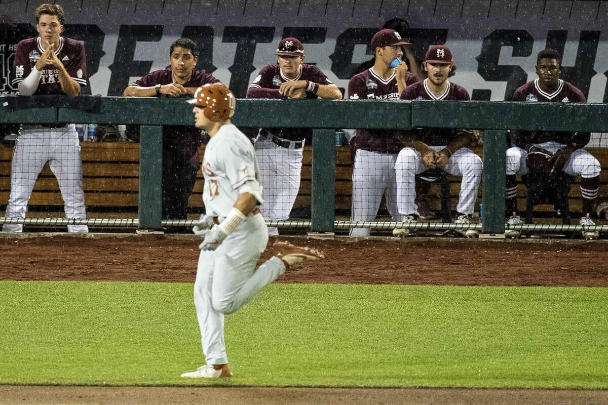 The Mississippi State dugout watches as Texas's Ivan Melendez rounds the bases after hitting a three-run home run during the ninth inning of a baseball game in the College World Series Friday, June 25, 2021, at TD Ameritrade Park in Omaha, Neb. (Chris Machian/Omaha World-Herald via AP)