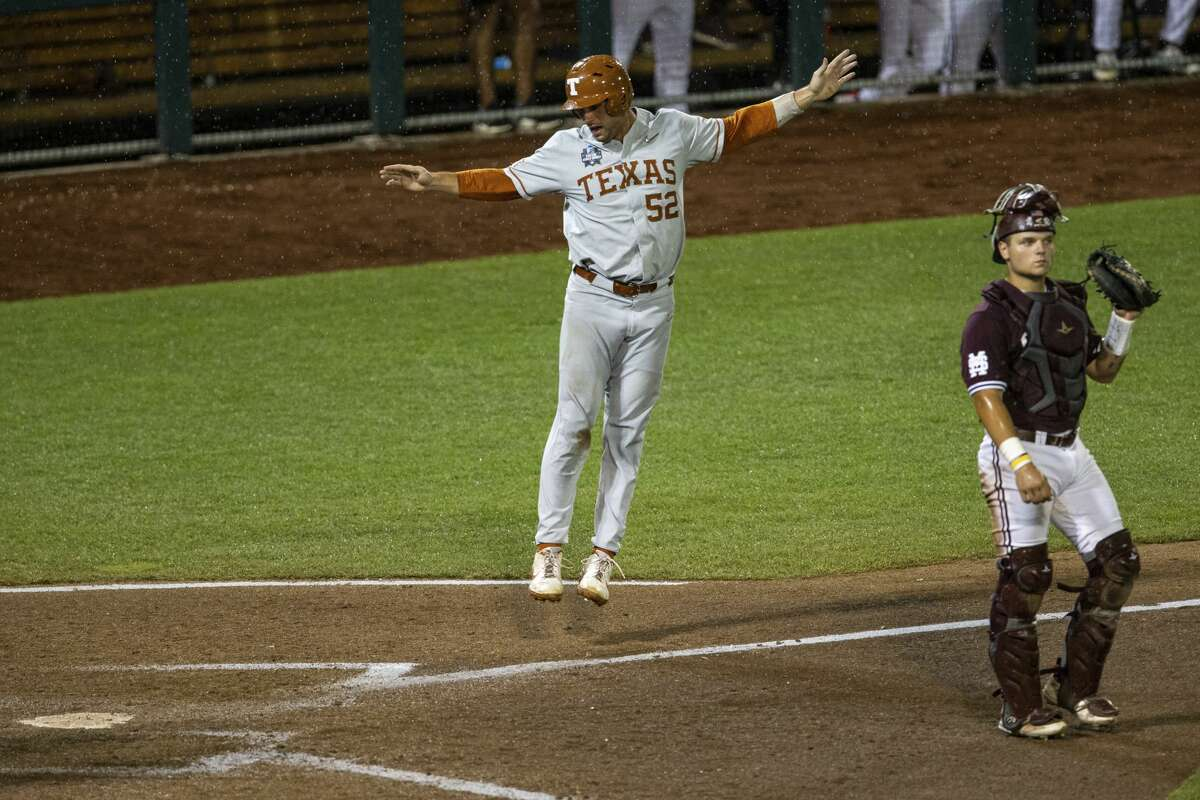Texas's Zach Zubia (52) scores from a from a home run by Ivan Melendez in the ninth with Mike Antico also scoring against Mississippi State with during a baseball game in the College World Series Friday, June 25, 2021, at TD Ameritrade Park in Omaha, Neb. (AP Photo/John Peterson)