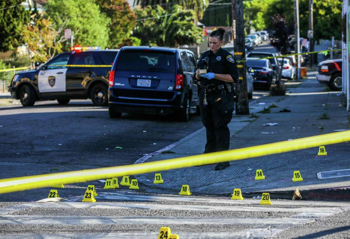 Oakland police Officer A. Goodard works a crime scene at School Street and Pleitner Avenue after a shooting. The city is shifting some money from the police budget to violence prevention and other services.