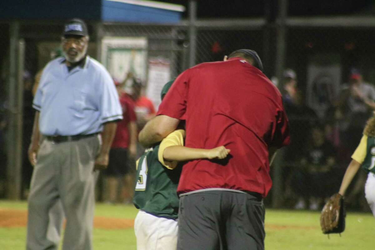 NASA 11s manager Mike Howard attempts to comfort Santa Fe pitcher Avin Bennett, who was one of the pitchers in the fateful sixth inning.