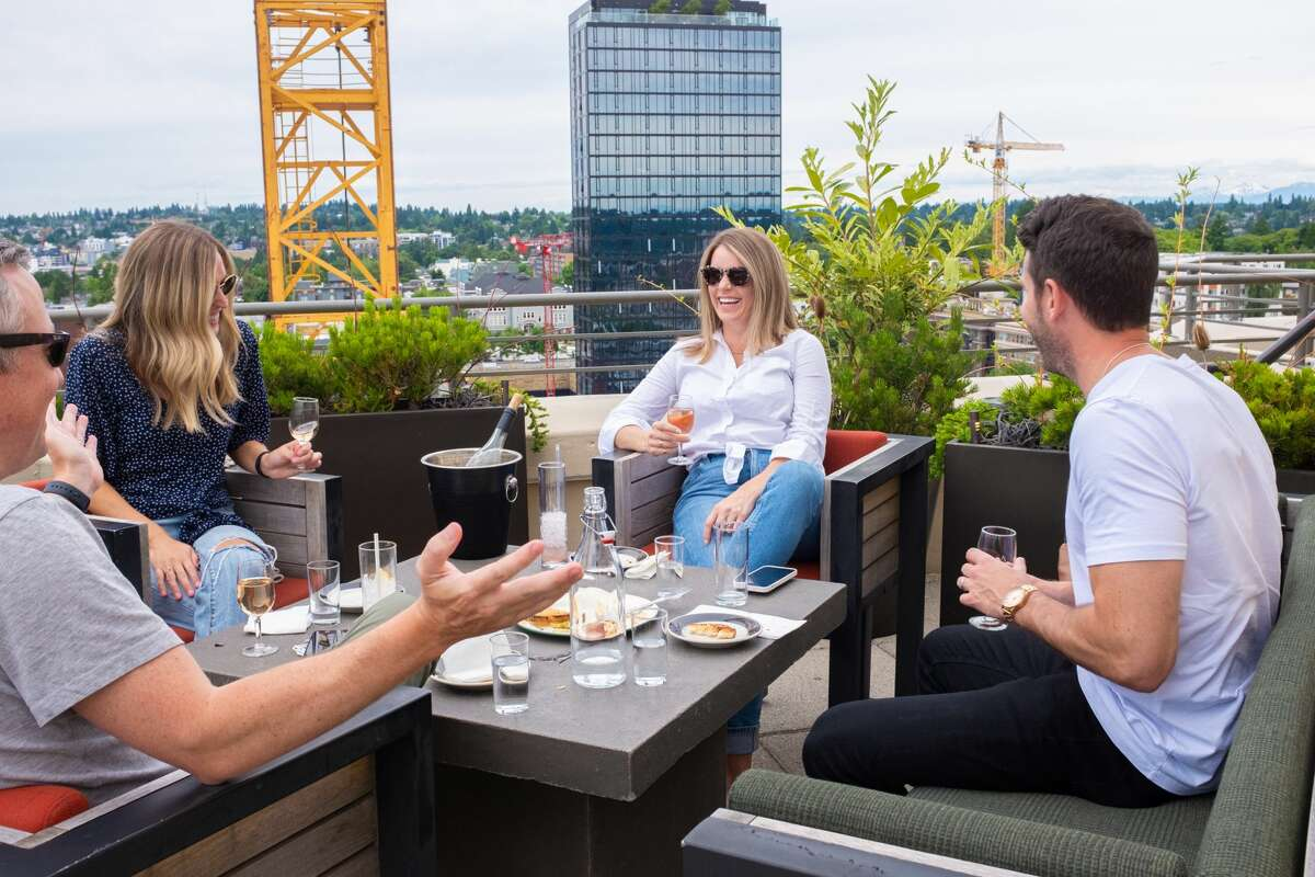 A group of people enjoy rooftop seating in the U District.