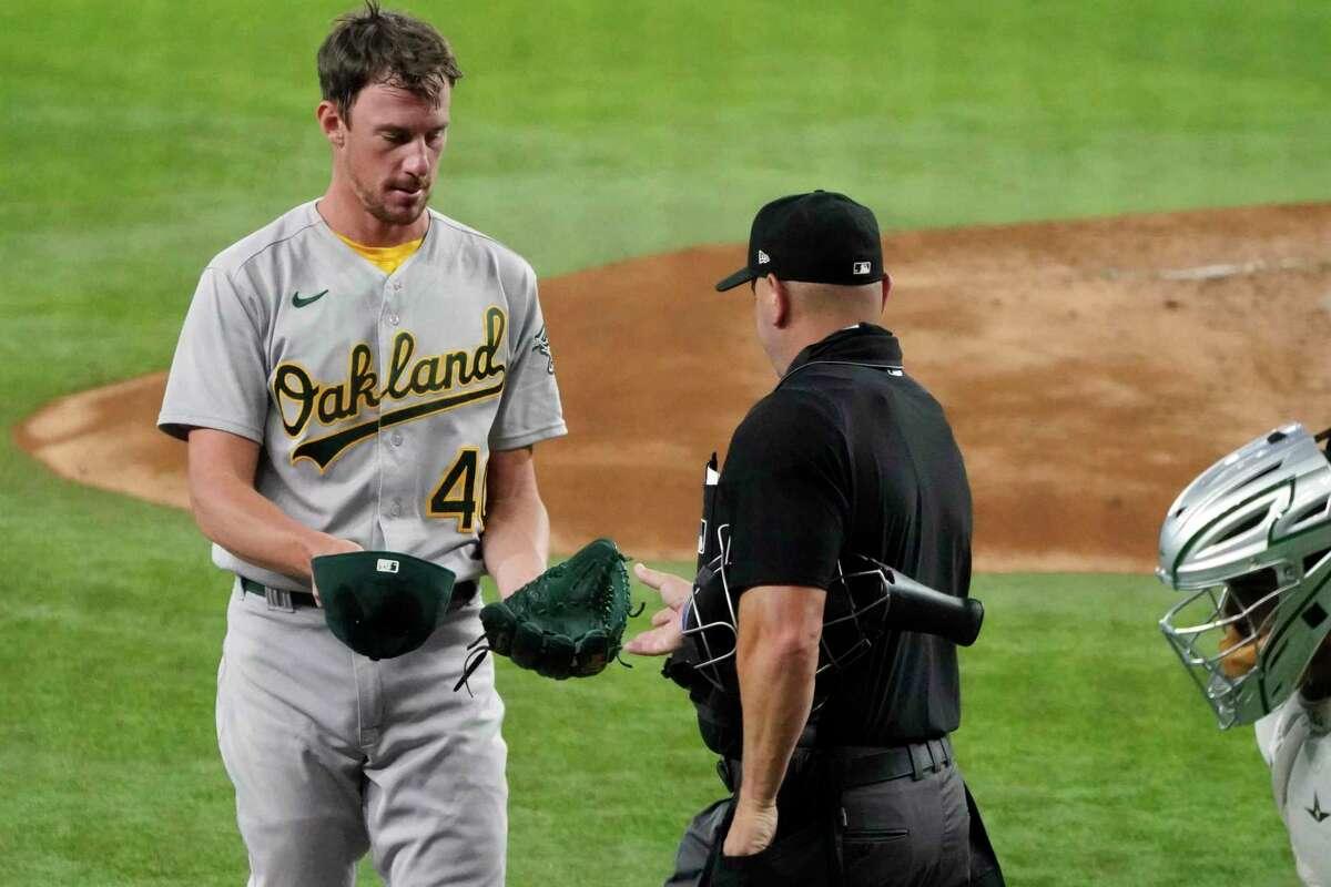 Umpire Scott Barry checks Oakland Athletics starting pitcher Chris Bassitt for illegal substances in the second inning of a baseball game Thursday, June 24, 2021, in Arlington, Texas. (AP Photo/Louis DeLuca)