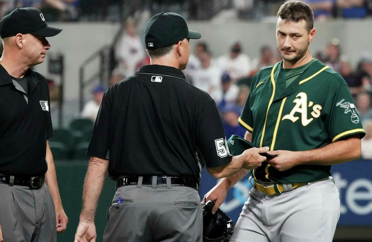Oakland Athletics relief pitcher Burch Smith has his glove and hat checked by the umpires after he pitches in the sixth inning against the Texas Rangers in a baseball game Tuesday, June 22, 2021, in Arlington, Texas. (AP Photo/Louis DeLuca)