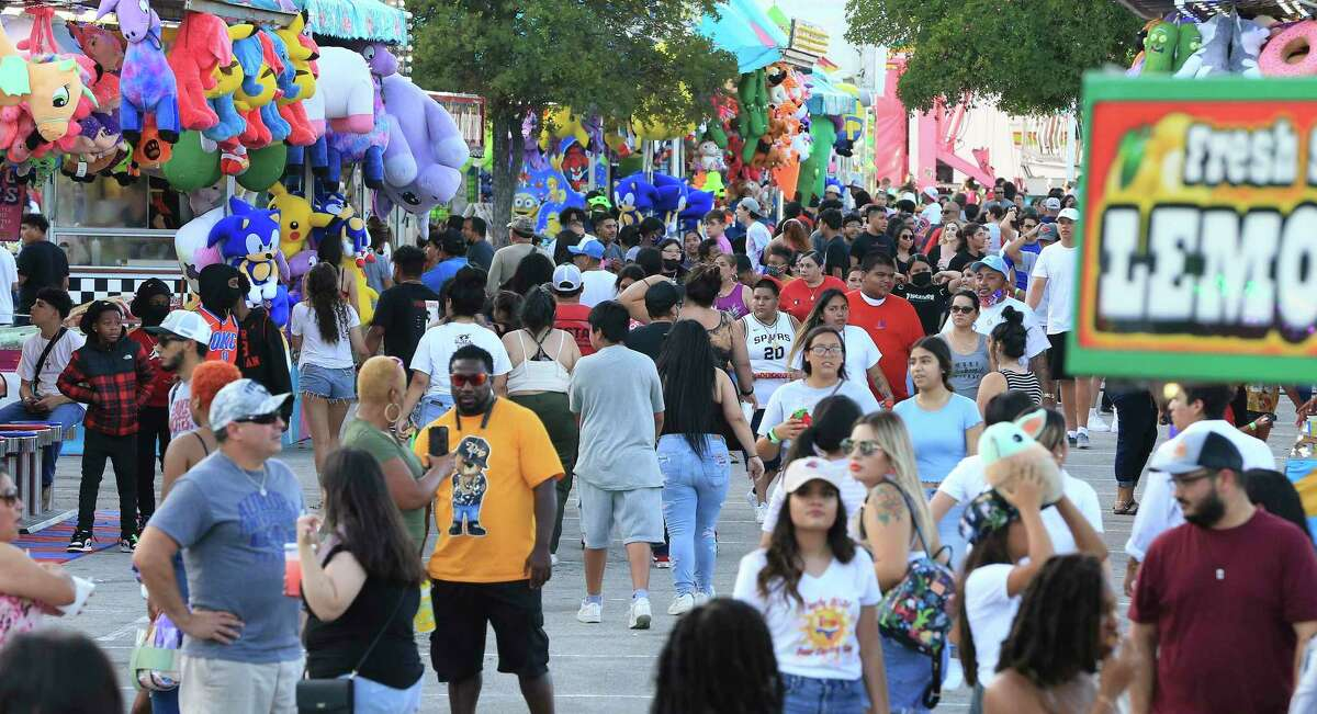 A crowd walks the midway at Fiesta Carnival at the Alamodome.