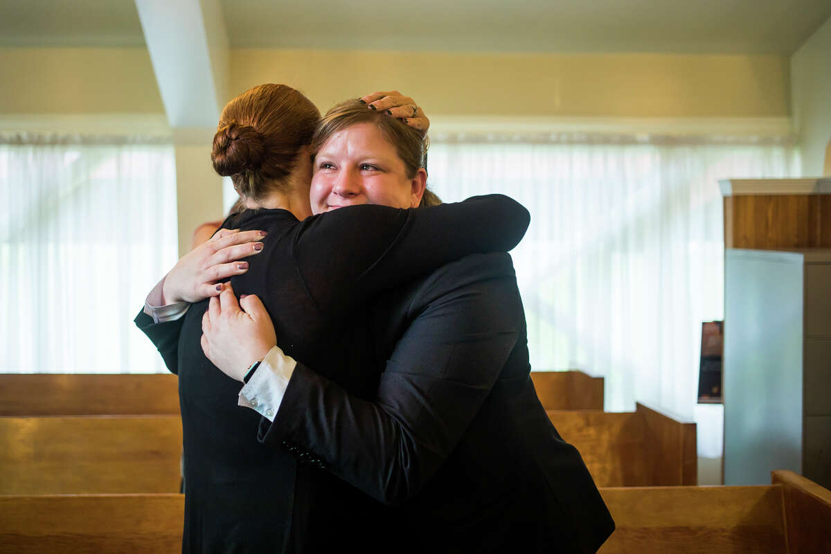 Ware-Smith-Woolever Funeral Director Becky Smith, right, hugs Elissa Biehl, family service counselor at Midland Memorial Gardens, left, after a ceremony honoring 15 individuals whose cremated remains had not been claimed, Friday, June 25, 2021 at Midland Memorial Gardens. The event was hosted by Ware-Smith-Woolever Funeral Directors.