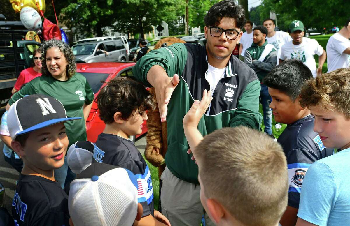 Supporters from the Cal Ripken team greet the Norwalk High School baseball team and state champions including Jaden Echevarria as the city hosts a parade and a reception at Norwalk Town Green Saturday, June 26, 2021, in Norwalk, Conn.
