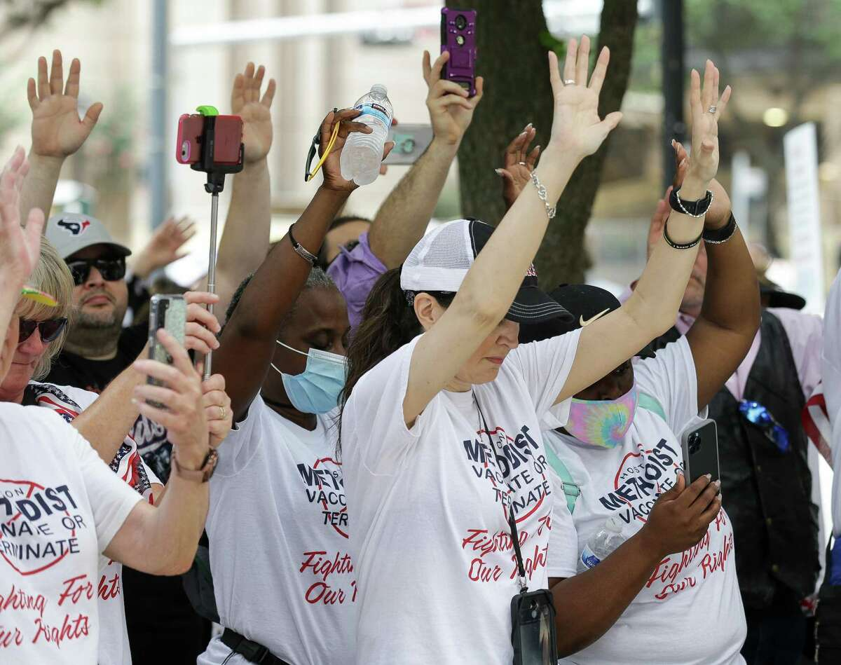 People raise their hands during a prayer while gathered outside Houston Methodist to protest the hospital's mandate that all staff must be vaccinated against COVID-19 or be terminated, on Saturday, June 26, 2021, in Houston.