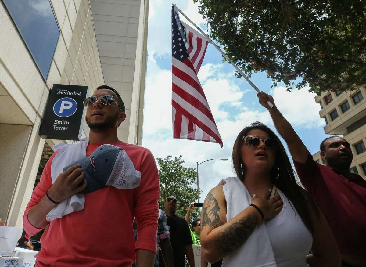 People sing the national anthem outside Houston Methodist, where they gathered to protest the hospital's mandate that all staff must be vaccinated against COVID-19 or be terminated, on Saturday, June 26, 2021, in Houston.