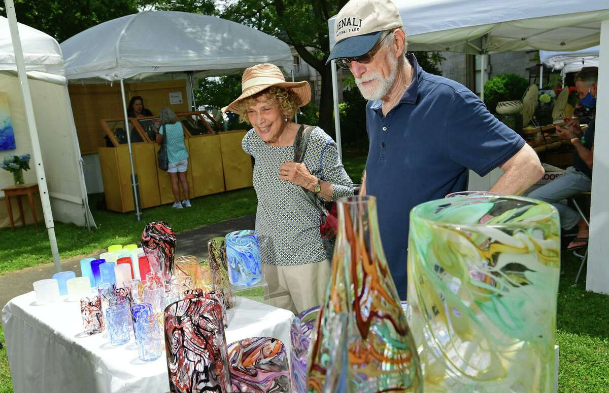 Jerry and Roni Liebowitza looka glasswares from artist Jason Curtis during The Norwalk Art Festival Saturday, June 26, 2021, at Mathews Park in Norwalk, Conn. The festival which continues Sunday features the works of 100 juried artists exhibiting a wide variety of media including, photography, drawing, ceramics, jewelry, painting, mixed media, printmaking, fiber, metal sculpture and glass. The Center for Contemporary Printmaking, Stepping Stones Museum, Mathews Mansion Museum and The Norwalk Parks Department, sponsored the festival.