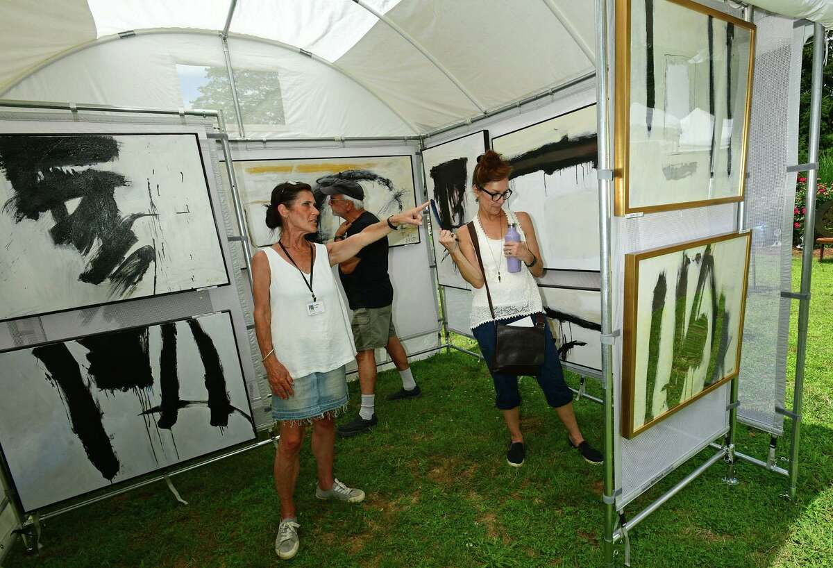 Artist Audrey Klotz points out her work to Tony and Mary Scimone during The Norwalk Art Festival Saturday, June 26, 2021, at Mathews Park in Norwalk, Conn. The festival which continues Sunday features the works of 100 juried artists exhibiting a wide variety of media including, photography, drawing, ceramics, jewelry, painting, mixed media, printmaking, fiber, metal sculpture and glass. The Center for Contemporary Printmaking, Stepping Stones Museum, Mathews Mansion Museum and The Norwalk Parks Department, sponsored the festival.