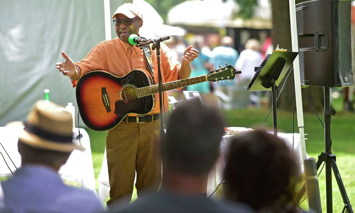 Musician and storyteller Neddy Smith spins a yarn during The Norwalk Art Festival Saturday, June 26, 2021, at Mathews Park in Norwalk, Conn. The festival which continues Sunday features the works of 100 juried artists exhibiting a wide variety of media including, photography, drawing, ceramics, jewelry, painting, mixed media, printmaking, fiber, metal sculpture and glass. The Center for Contemporary Printmaking, Stepping Stones Museum, Mathews Mansion Museum and The Norwalk Parks Department, sponsored the festival.