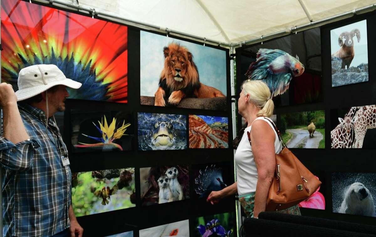 Bruce Franklin greets Norwalk resident Dawn Del Greco as she looks at his work during the Norwalk Art Festival on Saturday at Mathews Park in Norwalk. The festival which continues Sunday, features the works of 100 juried artists exhibiting a wide variety of media including, photography, drawing, ceramics, jewelry, painting, mixed media, printmaking, fiber, metal sculpture and glass. The Center for Contemporary Printmaking, Stepping Stones Museum, Mathews Mansion Museum and The Norwalk Parks Department sponsored the festival.