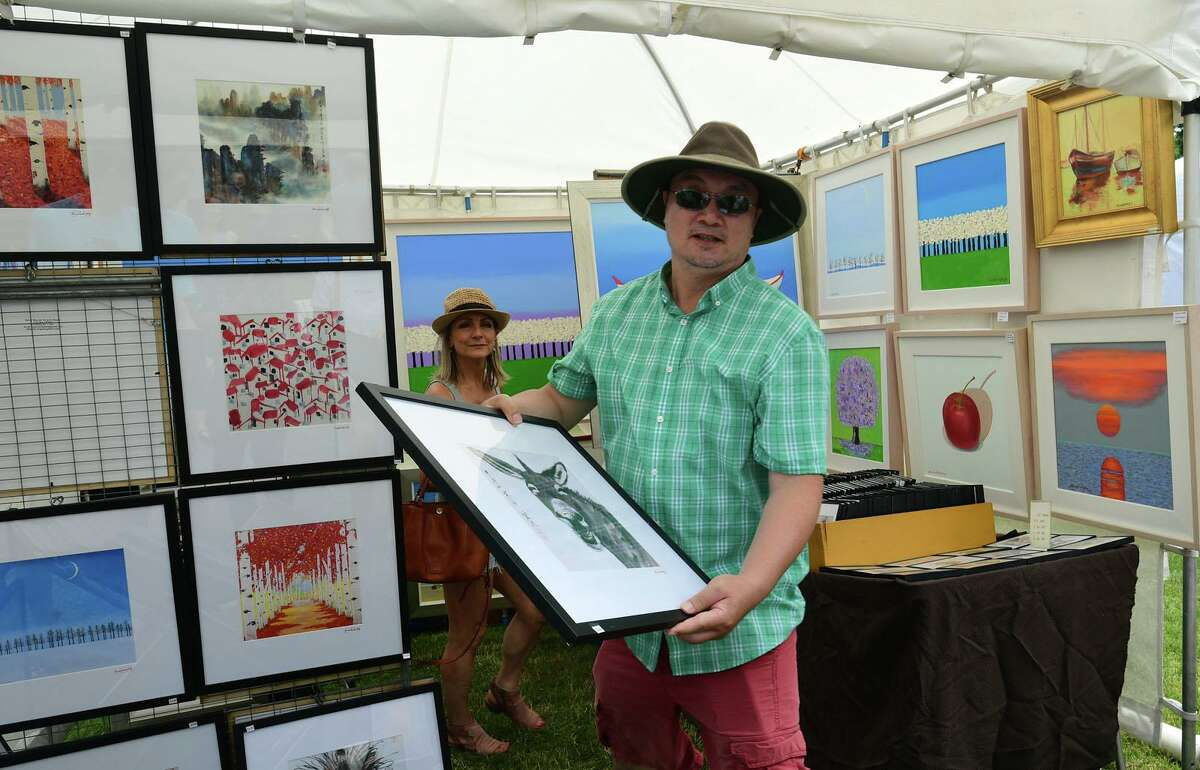 Aitist Simon Weng shows of his prints during the Norwalk Art Festival on Saturday.