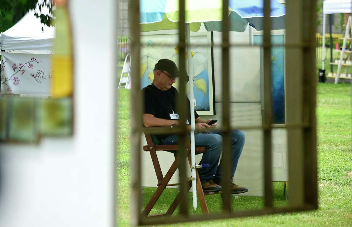 Painter David Gordon stays out of the sun during The Norwalk Art Festival Saturday, June 26, 2021, at Mathews Park in Norwalk, Conn. The festival which continues Sunday features the works of 100 juried artists exhibiting a wide variety of media including, photography, drawing, ceramics, jewelry, painting, mixed media, printmaking, fiber, metal sculpture and glass. The Center for Contemporary Printmaking, Stepping Stones Museum, Mathews Mansion Museum and The Norwalk Parks Department, sponsored the festival.