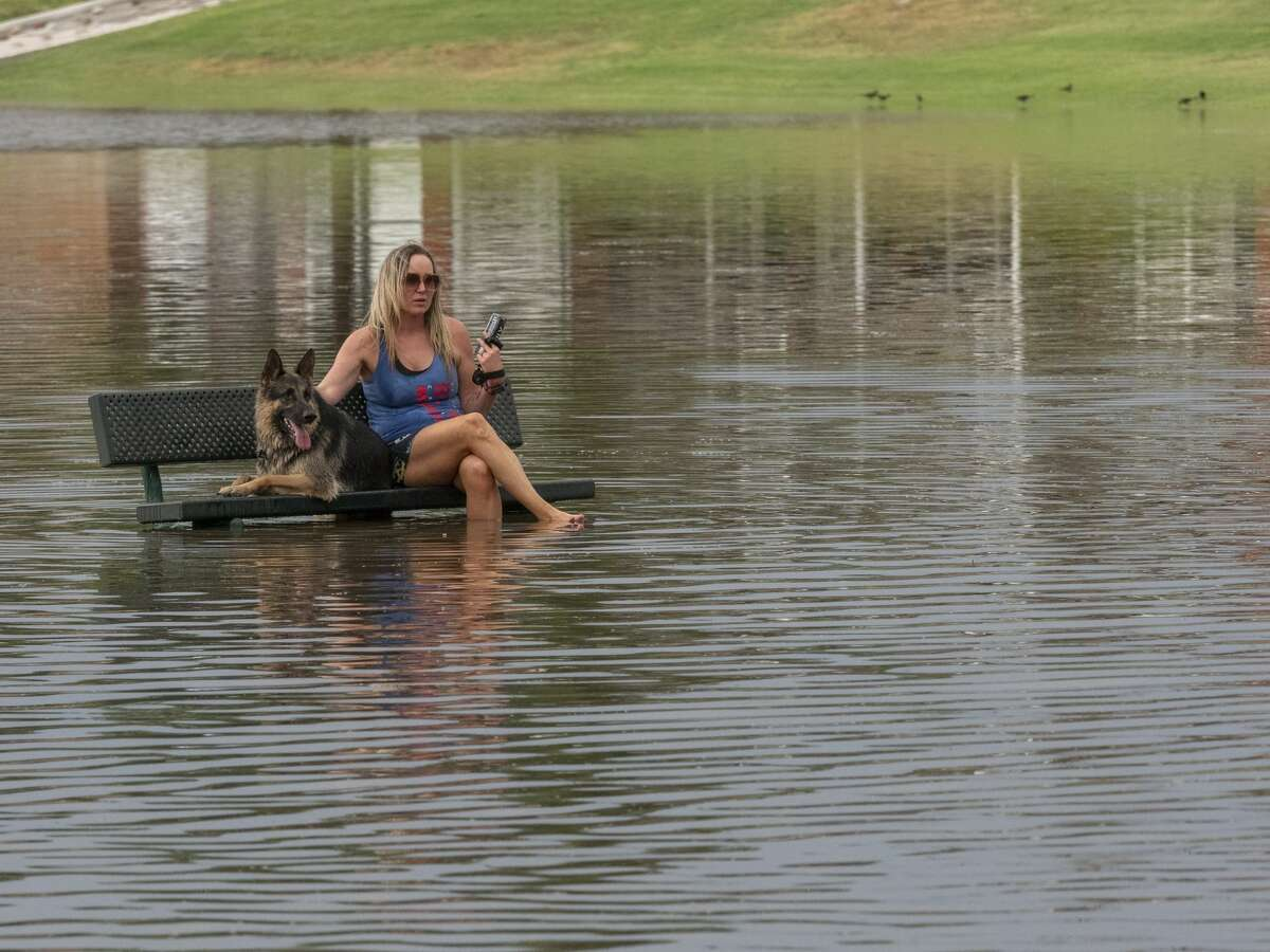 Heavy rains 06/26/2021 flooded streets and filled area parks, as Jessica Conner and Arlo take a rest on a park bench in Cowden Park after playing in the water. Tim Fischer/Reporter-Telegram