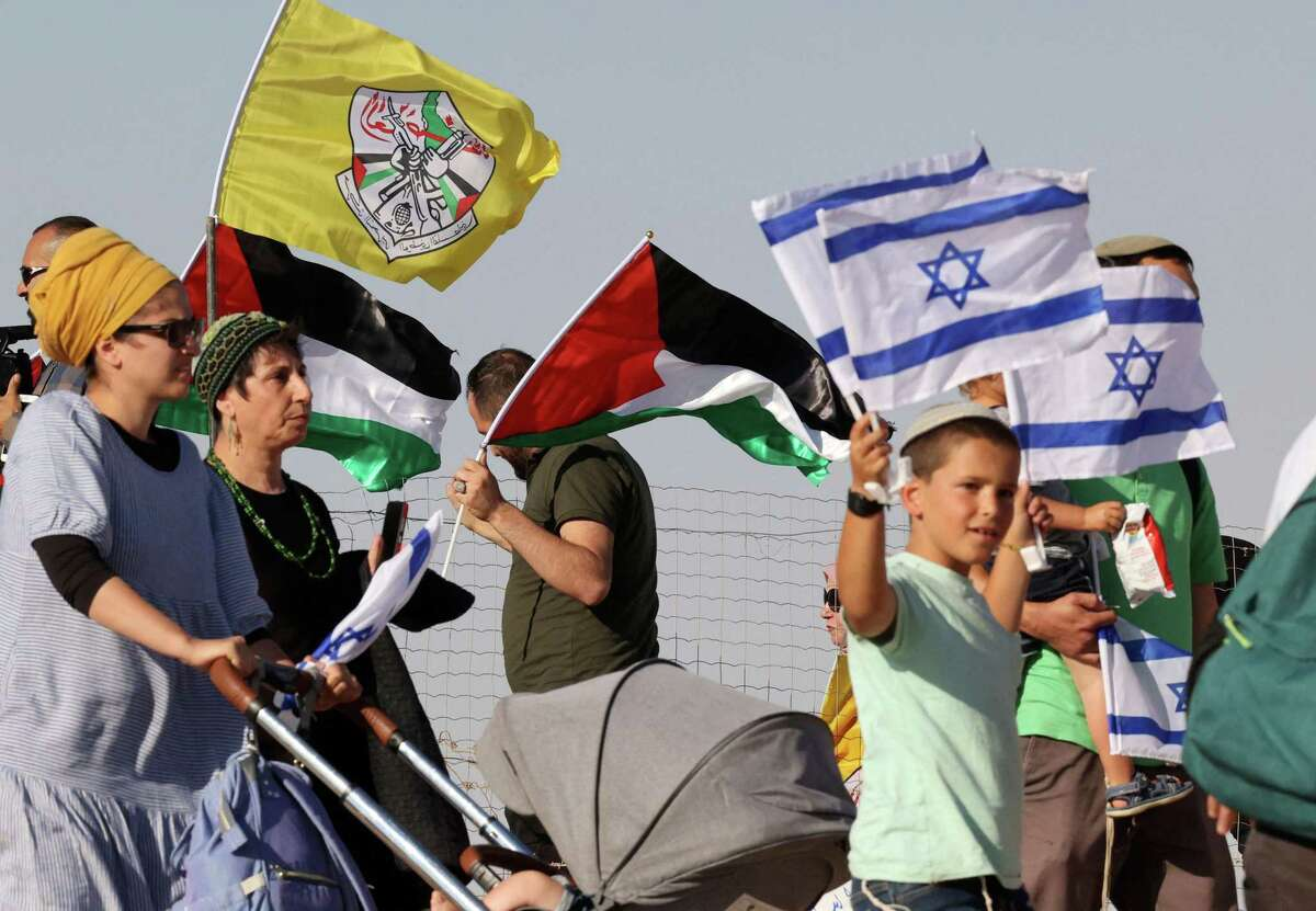 Israeli settlers carrying flags walk past Palestinians holding the Fatah party and the Palestinian flag, during a march by Jewish settlers amid Palestinian lands south of the village of Yatta, near Hebron in the occupied West Bank.