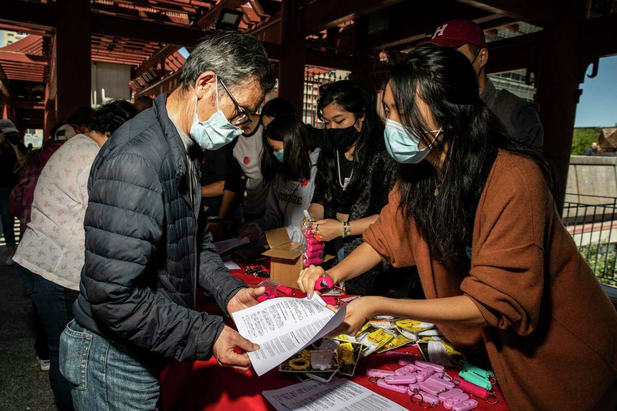 Victoria Yuan, right, explains how to use pepper spray to an attendee during the AAPI Care Fair in Chinatown's Portsmouth Square in San Francisco, Calif. Saturday, June 26, 2021.