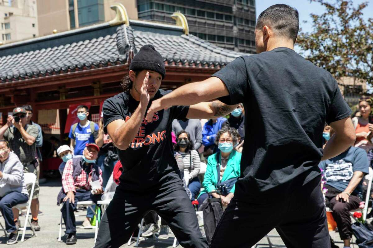 Jeremy Jong, left, and brother Ritchie Jong, with Asians Are Strong, demonstrate personal defensive tactics during the AAPI Care Fair in Chinatown's Portsmouth Square in San Francisco, Calif. Saturday, June 26, 2021.