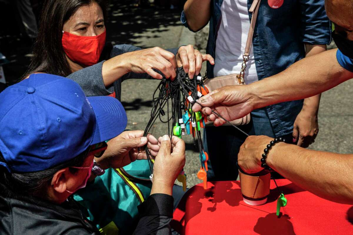 Volunteers untangle a bundle of whistles during the AAPI Care Fair at Portsmouth Square in Chinatown's Portsmouth Square in San Francisco, Calif. Saturday, June 26, 2021.