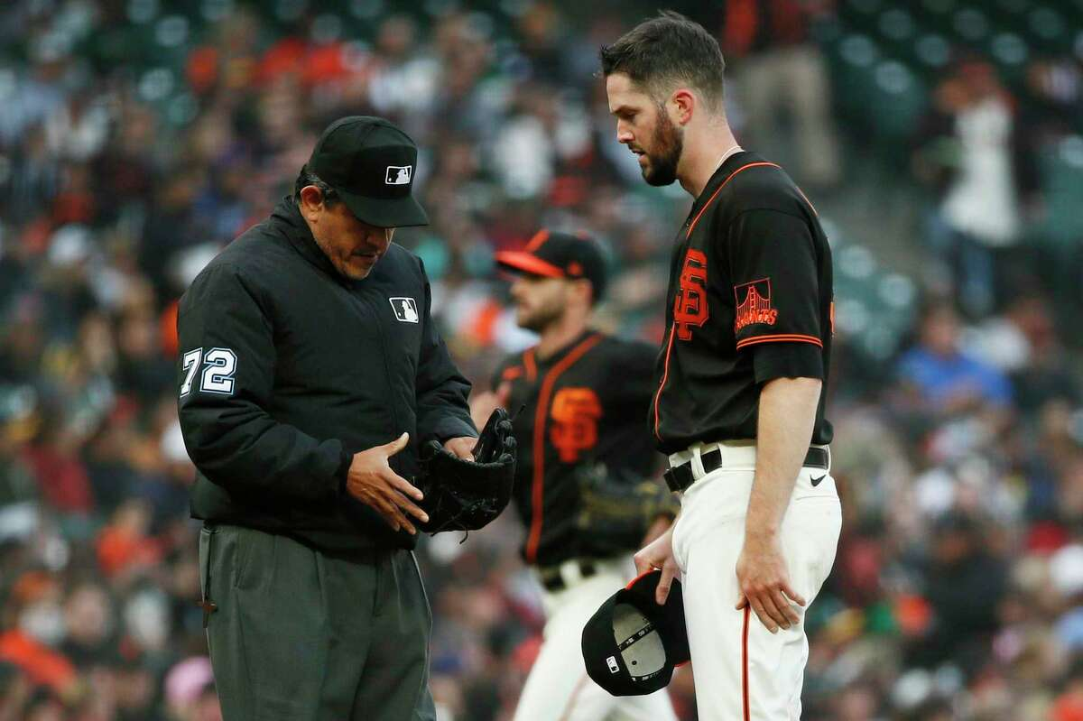 From left: Umpire Alfonso Marquez (72) checks the hat, glove and belt of San Francisco Giants starting pitcher Alex Wood (57) for illegal substances after the first inning during an MLB game against the Oakland Athletics at Oracle Park, Saturday, June 26, 2021, in San Francisco, Calif. Umpires continue to check MLB pitchers for sticky substances that may help aid a pitcher's grip or baseball spin.