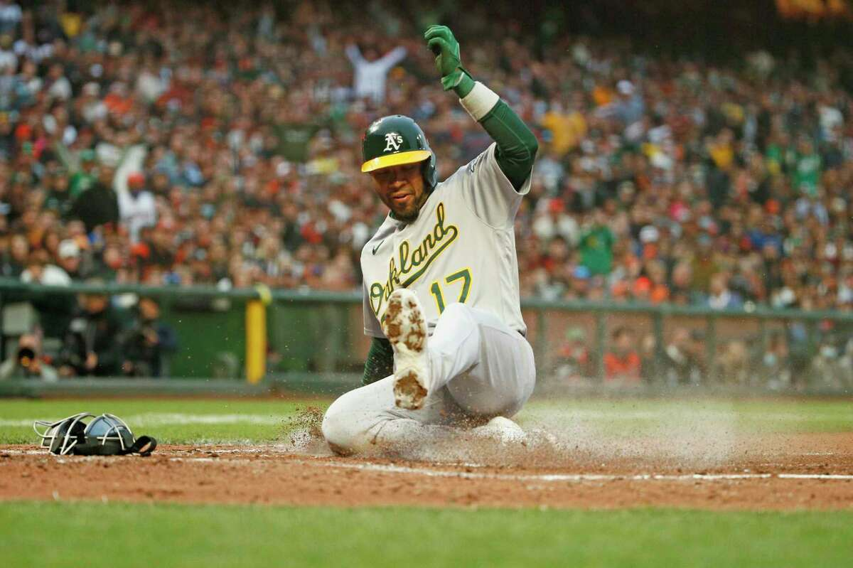 Oakland Athletics Elvis Andrus (17) slides to home plate after a wild pitch by San Francisco Giants starting pitcher Alex Wood (57) in the third inning during an MLB game at Oracle Park, Saturday, June 26, 2021, in San Francisco, Calif.
