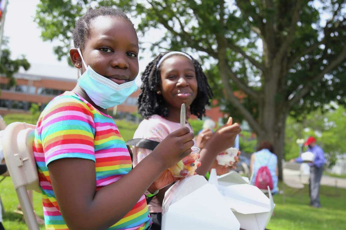 Joanne Otieno, 9, left, of New York City, and her sister Ellen, 10, enjoy a snack at the 56th jUNe Day Celebration ceremony on Jesup Green on Saturday, June 26, 2021 in Westport, Conn.