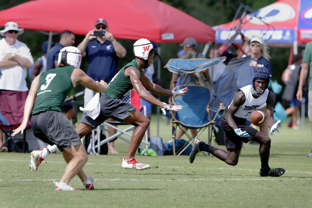A Tompkins player, right, makes a catch with Woodlands players, left, in pursuit during their second round game in the 7-on-7 state tournament held at Veterans Park Saturday, Jun. 26, 2021 in College Station, TX.