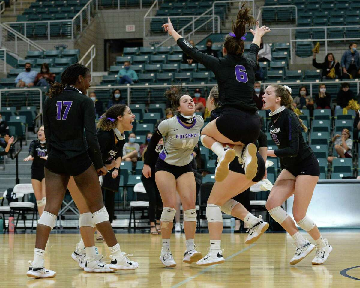 The Fulshear Charges celebrate after winning the first set of the Class 5A state semifinal volleyball match against the Dripping Springs Tigers on Tuesday, December 8, 2020 at Leonard Merrell Center, Katy, TX.