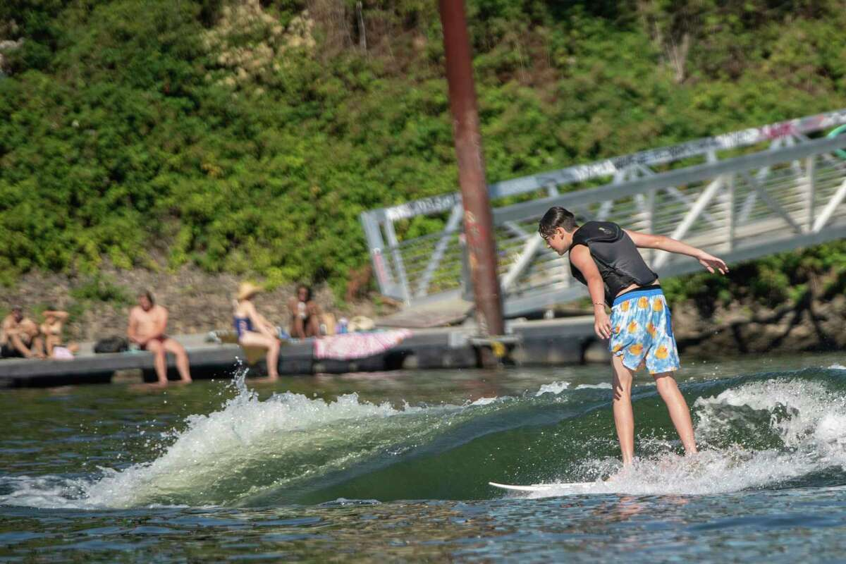 As a heat wave cooked Portland, Ore., on Friday, June 25, 2021, water-seekers took to the Willamette River for relief. Jet skis, speed boats, paddle-boards, sailors and beachgoers could be seen stretching from the Hawthorne Bridge to the south of Ross Island. (Mark Graves/The Oregonian via AP)