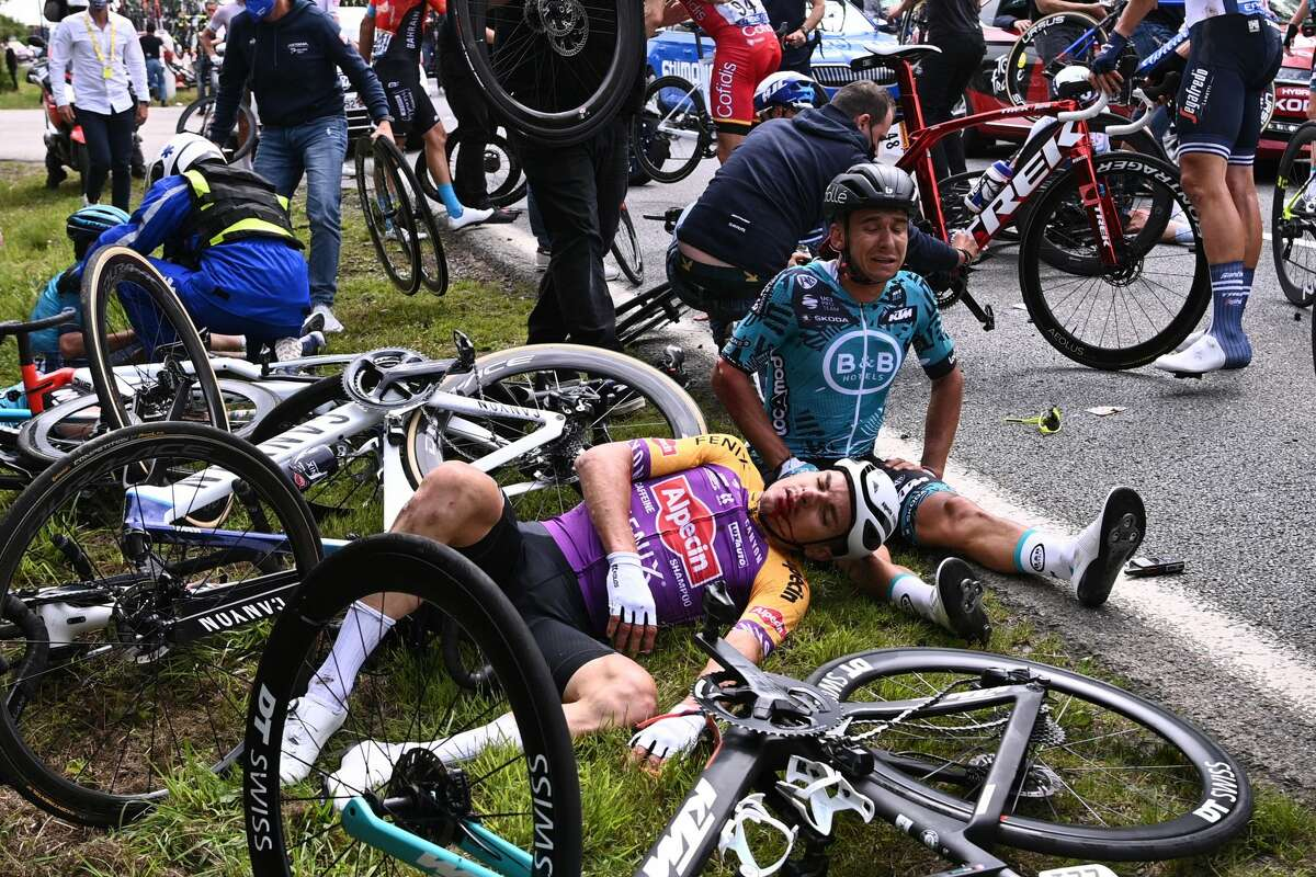 Team B&B KTM's Bryan Coquard of France (R) and a Team Alpecin Fenix' rider lie on the ground after crashing during the 1st stage of the 108th edition of the Tour de France cycling race, 197 km between Brest and Landerneau, on June 26, 2021.