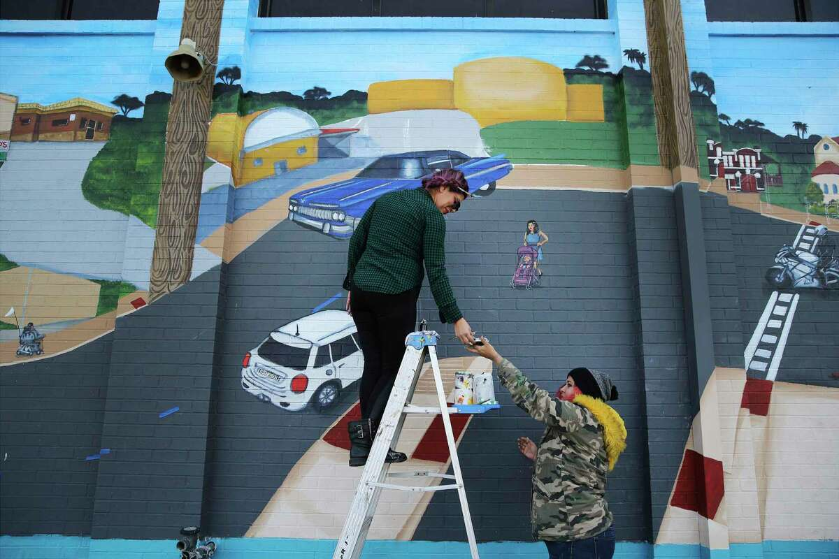 Artist April Ceja (top) and lead artist Crystal Tamez put the finishing touches on a mural dedicated to pedestrians and cyclists killed on Culebra Road. The mural, at a fire station, was completed in 2019.