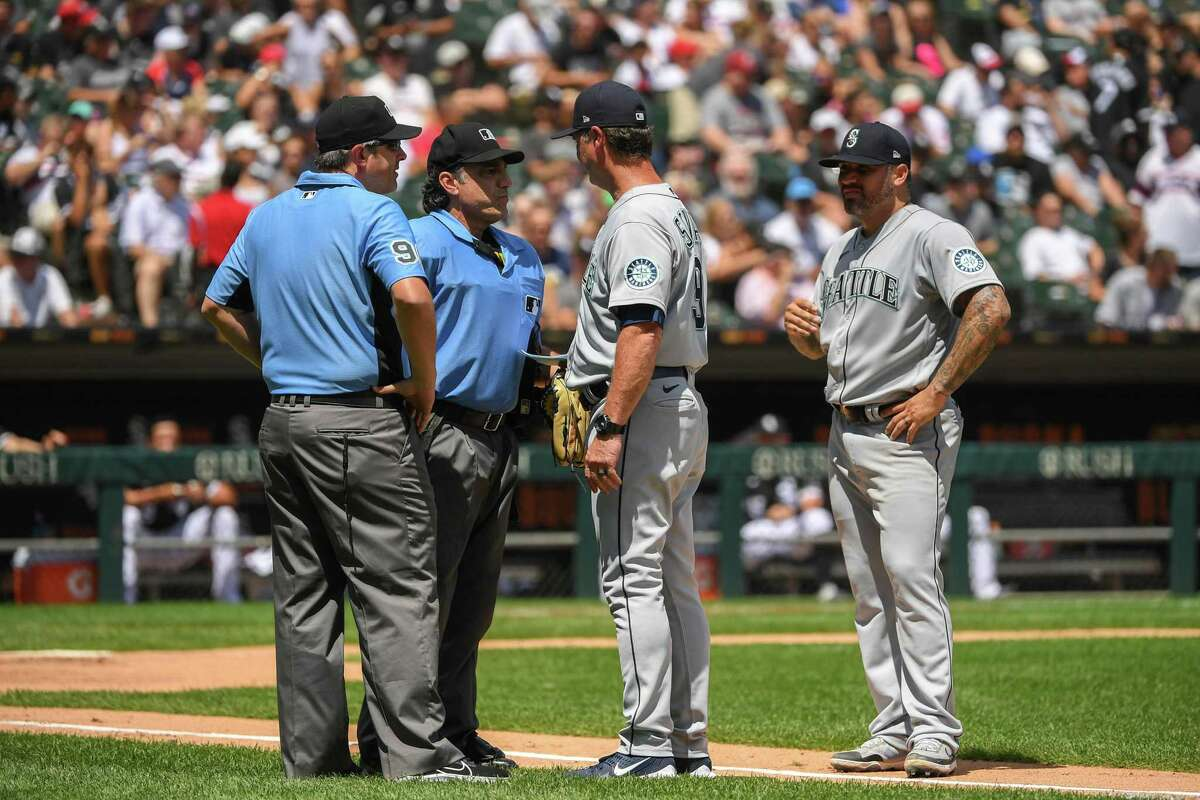 Umpires Phil Cuzzi, center, Brian Gorman, left, talk to Mariners manager Scott Servais before ejecting Hector Santiago, right, after finding a substance on his glove in the fifth inning against the Chicago White Sox at Guaranteed Rate Field on Sunday.