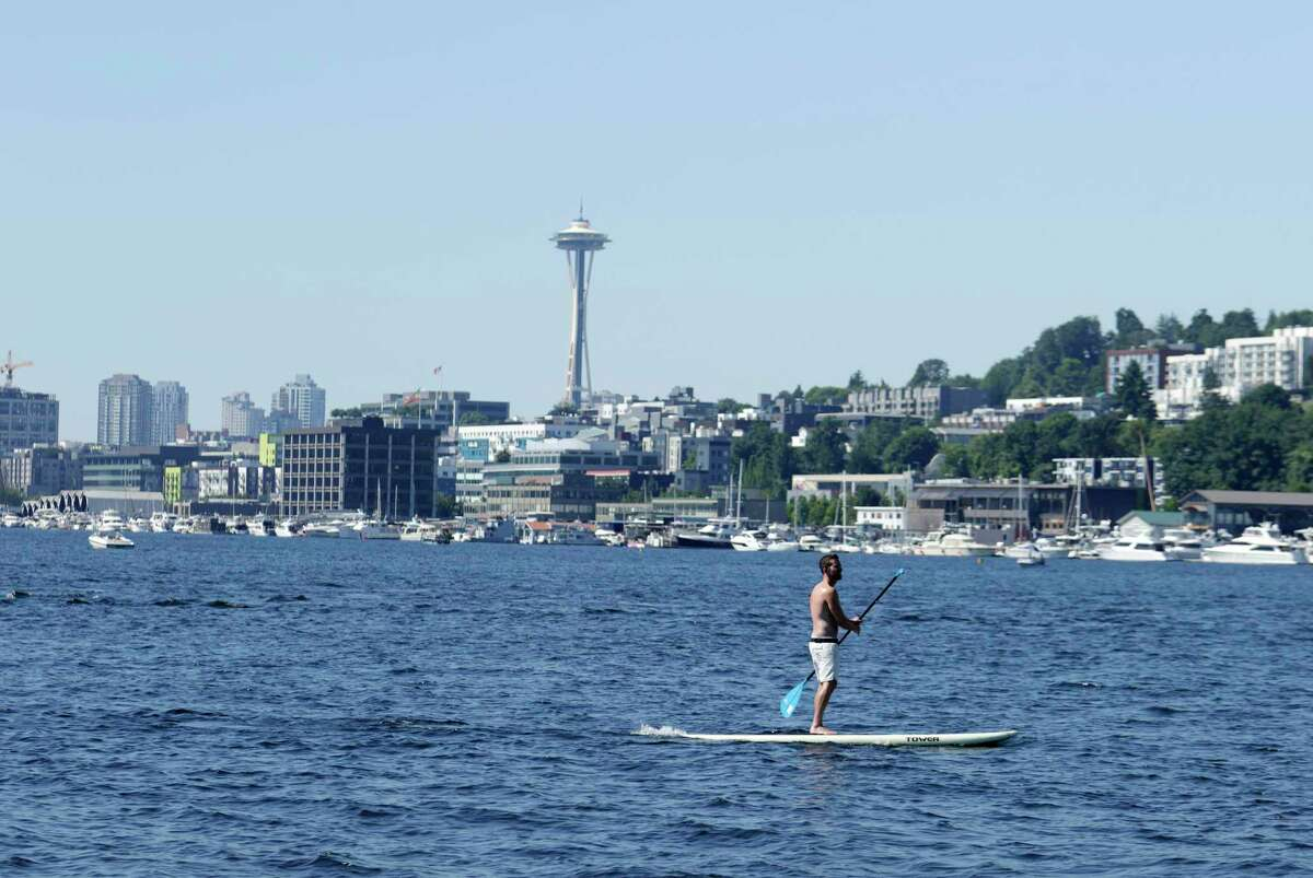 A person rides on a paddle board on Lake Union during a heat wave hitting the Pacific Northwest, Sunday, June 27, 2021, in Seattle. Yesterday set a record high for the day with more record highs expected today and Monday.