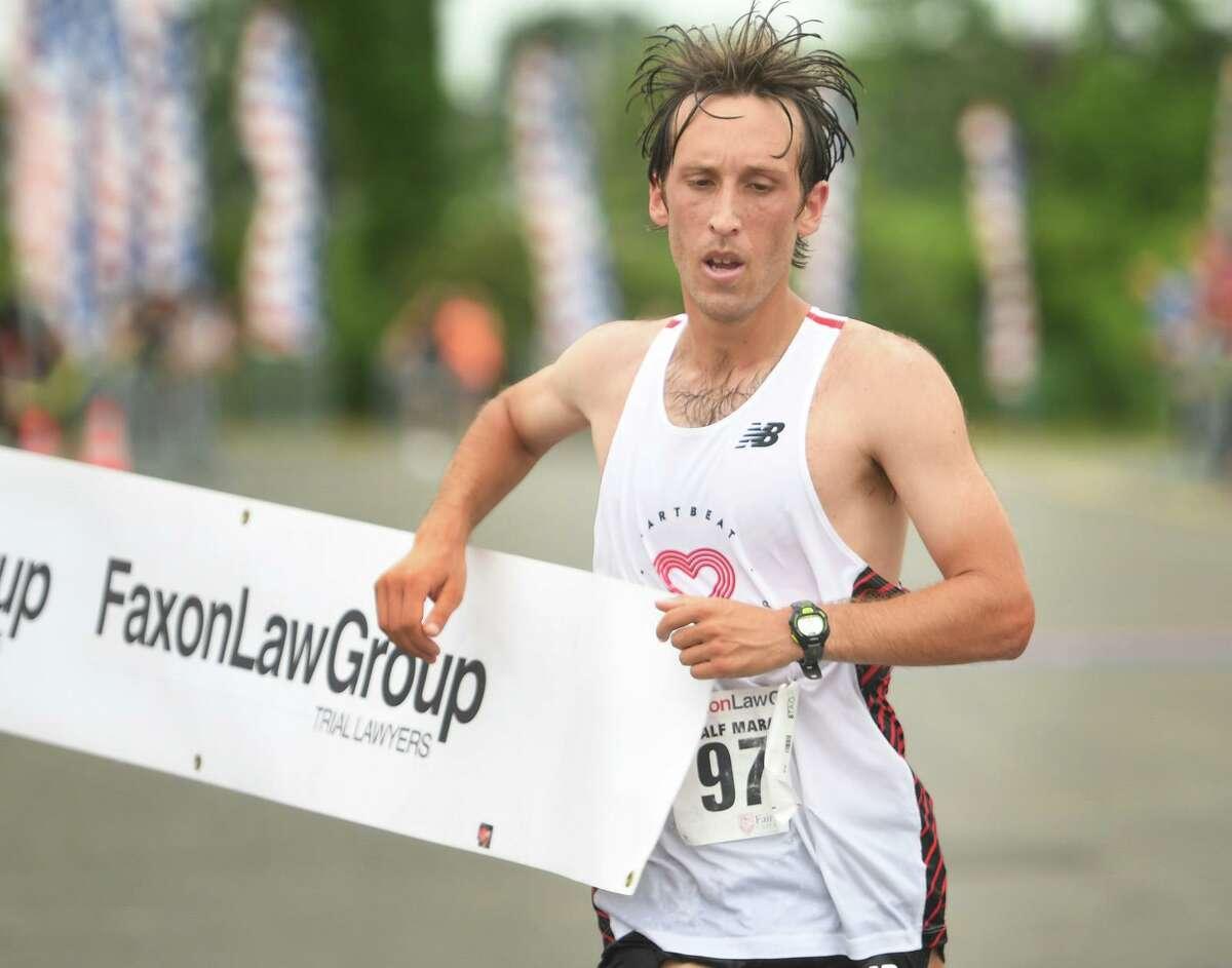 Everett Hackett, of Hartford, breaks the tape to win the Fairfield Half Marathon on Sunday at Jennings Beach in Fairfield.