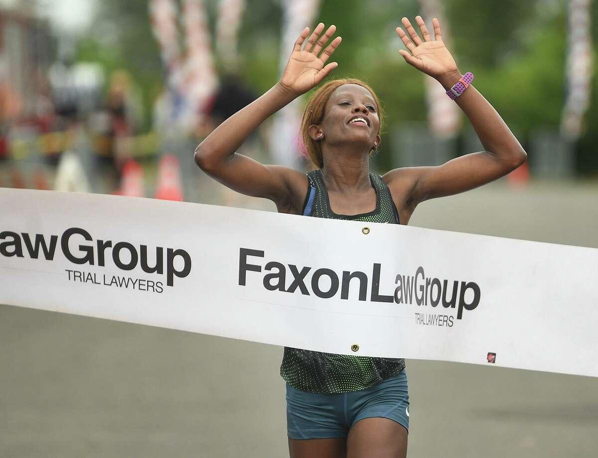 Monicah Ngige, of Lansing, MI, breaks the tape to win the Fairfield Half Marathon.
