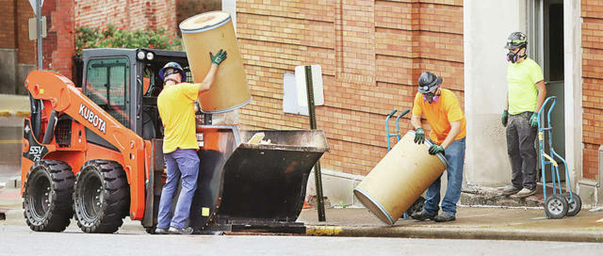 Workers dump building materials into a dumpster Friday while doing renovation work inside the Wedge Building in downtown Alton. Unemployment in the Metro East fell to 4.6 percent in May, according to the Illinois Department of Employment Security and U.S. Bureau of Labor Statistics.