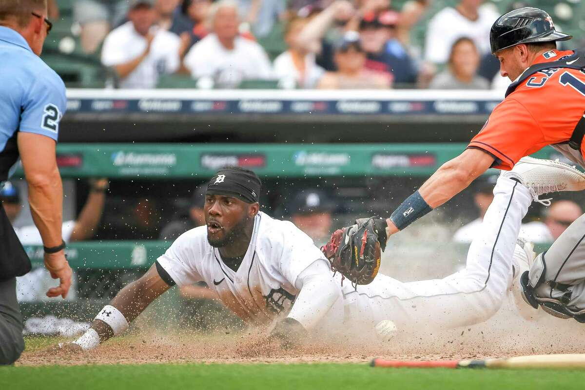 DETROIT, MICHIGAN - JUNE 27: Akil Baddoo #60 of the Detroit Tigers scores a run on a sacrifice bunt by Robbie Grossman #8 of the Detroit Tigers to win the game against the Houston Astros during the bottom of the tenth inning at Comerica Park on June 27, 2021 in Detroit, Michigan.