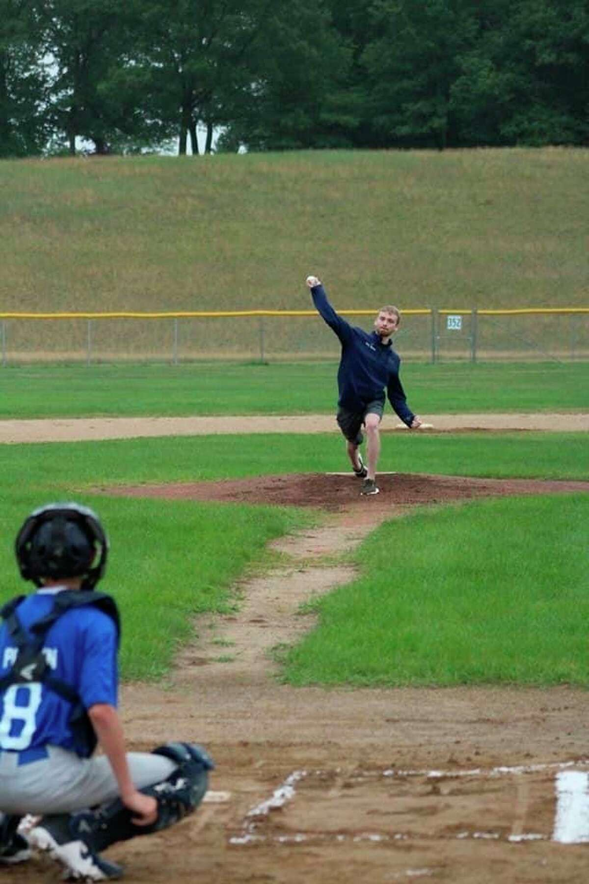Jeff Stewart's sonIainthrows out the first pitch at Manistee's weekend youth baseball tournament on Friday. (Courtesy photo)