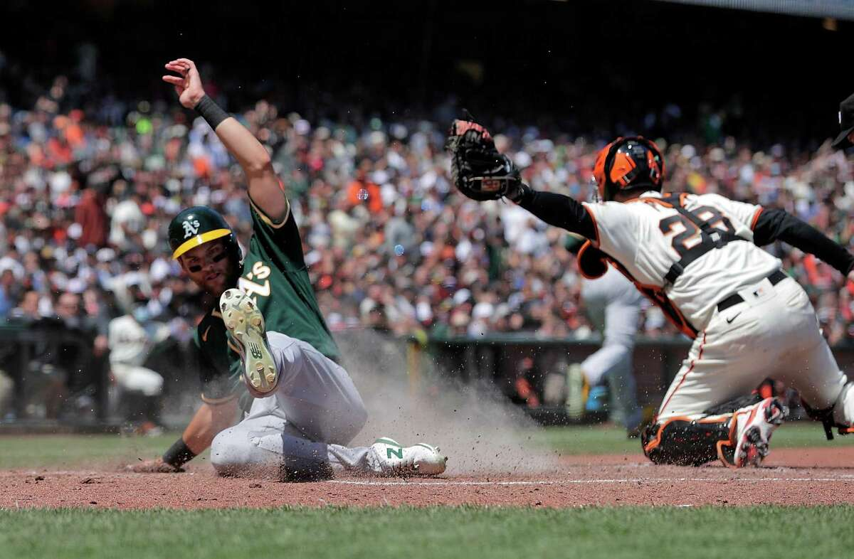 Chad Pinder (4) scores past the swipe tag attempt by Buster Posey (28) on a single by Aramis Garcia (37) in the sixth inning as the San Francisco Giants played the Oakland Athletics at Oracle Park in San Francisco, Calif., on Sunday, June 27, 2021.