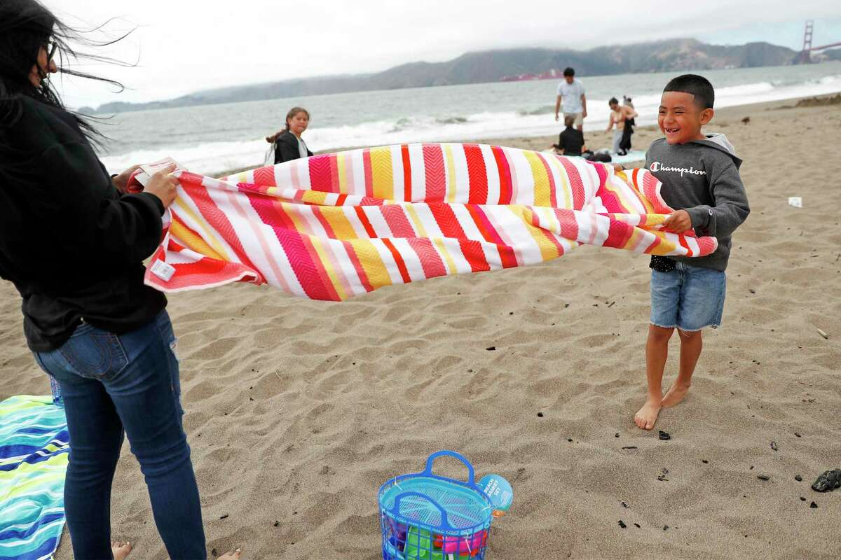 Kaydin Gonzalez, 7, and his sister, Mariah, try to fold a beach towel as the wind gusts at Baker Beach in San Francisco, Calif., on Sunday, June 27, 2021. While some parts of Bay Area were having a heat wave, temperatures stayed in the 60s in San Francisco.
