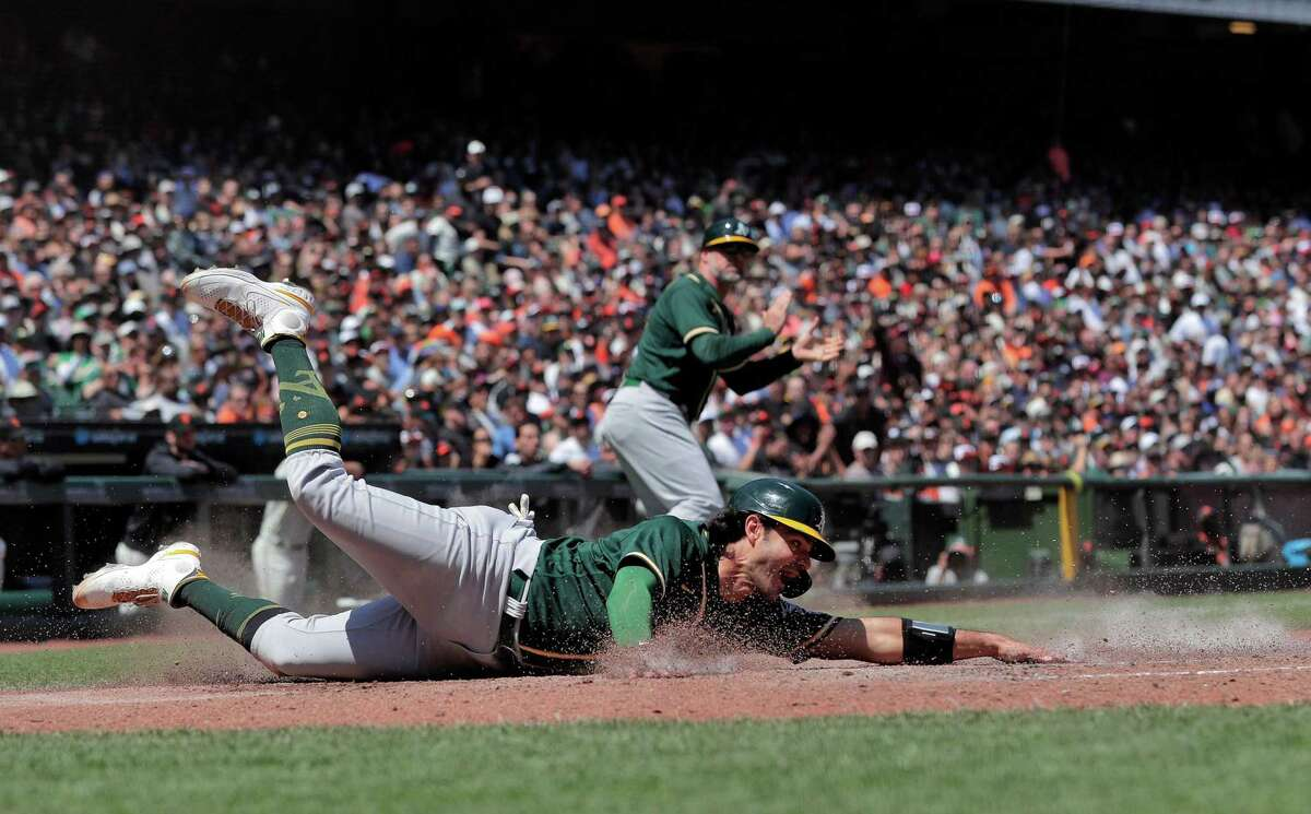 Aramis Garcia (37) reaches back to tag the plat to score on a hit by Elvis Andrus (17) in the sixzth inning as the San Francisco Giants played the Oakland Athletics at Oracle Park in San Francisco, Calif., on Sunday, June 27, 2021.