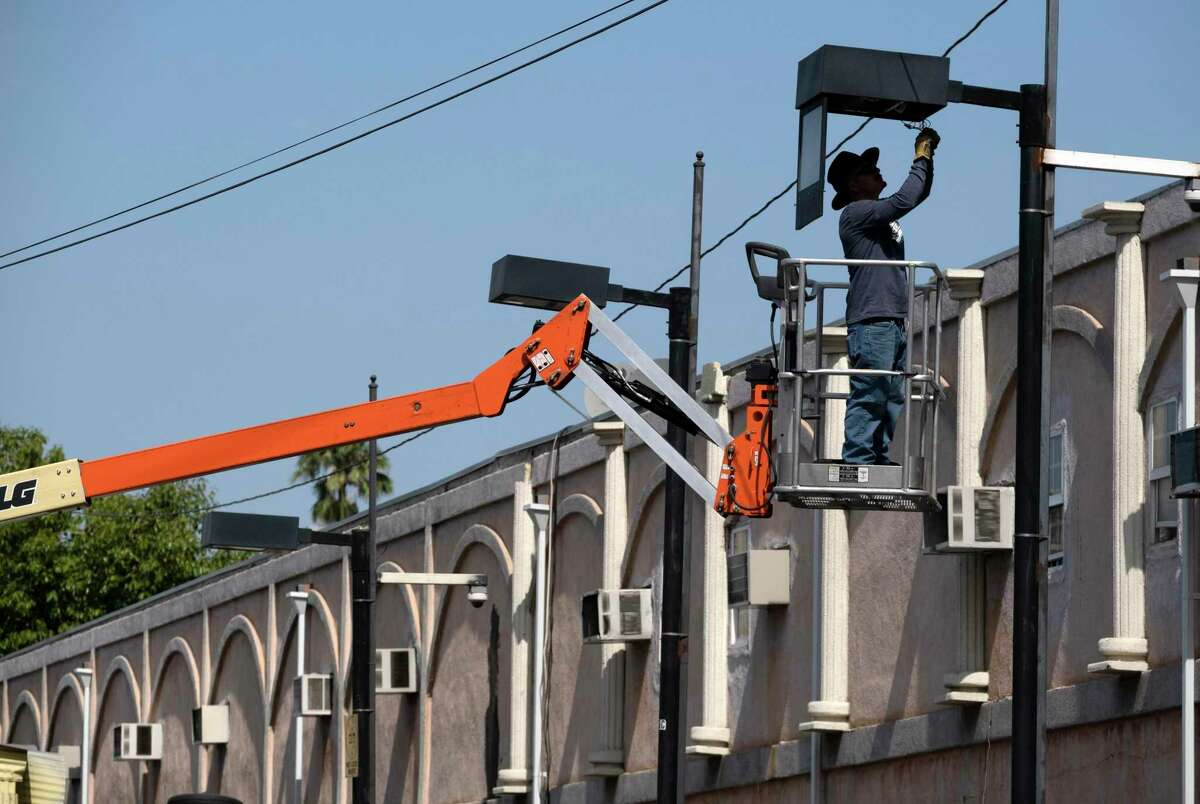 A worker fixes a street lamp in Los Angeles. California's power grid operator said voluntary energy conservation might be called for as as a heat wave bakes the Pacific Northwest and parts of California.