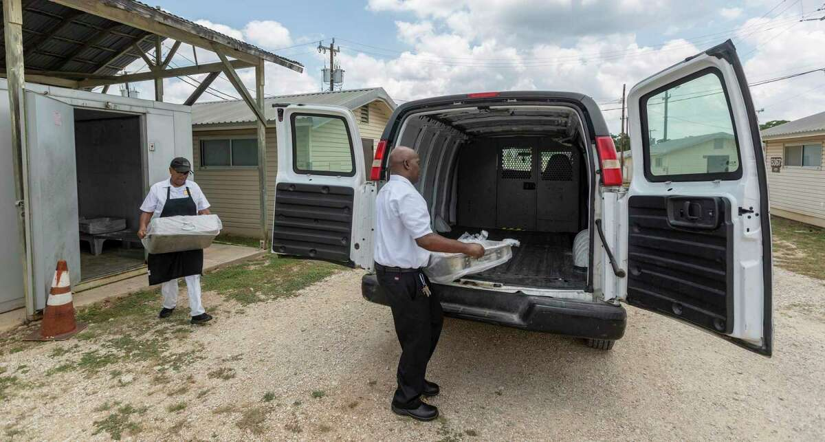 Shambra Trabue, left, and Ronald Lawson get meat from an outdoor cooler Thursday and place it in a van for transportation as they prepare dinner meals at the Joint Base San Antonio-Camp Bullis dining facility. Camp Bullis has been given $22 million to build a new dining facility.