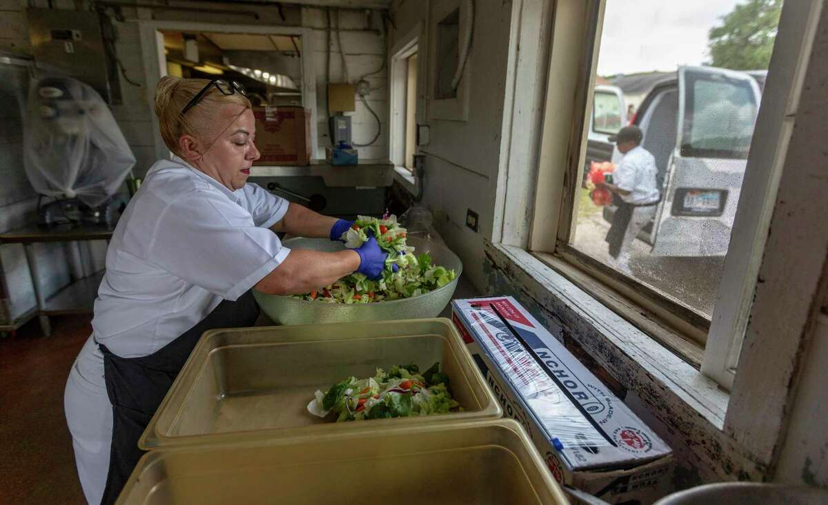 Magdalena Martinez, left, prepares salads Thursday inside the Joint Base San Antonio-Camp Bullis dining facility as Shambra Trabue unloads food from a van outside the building. Congress has appropriated $22 million to build a new dining facility. .