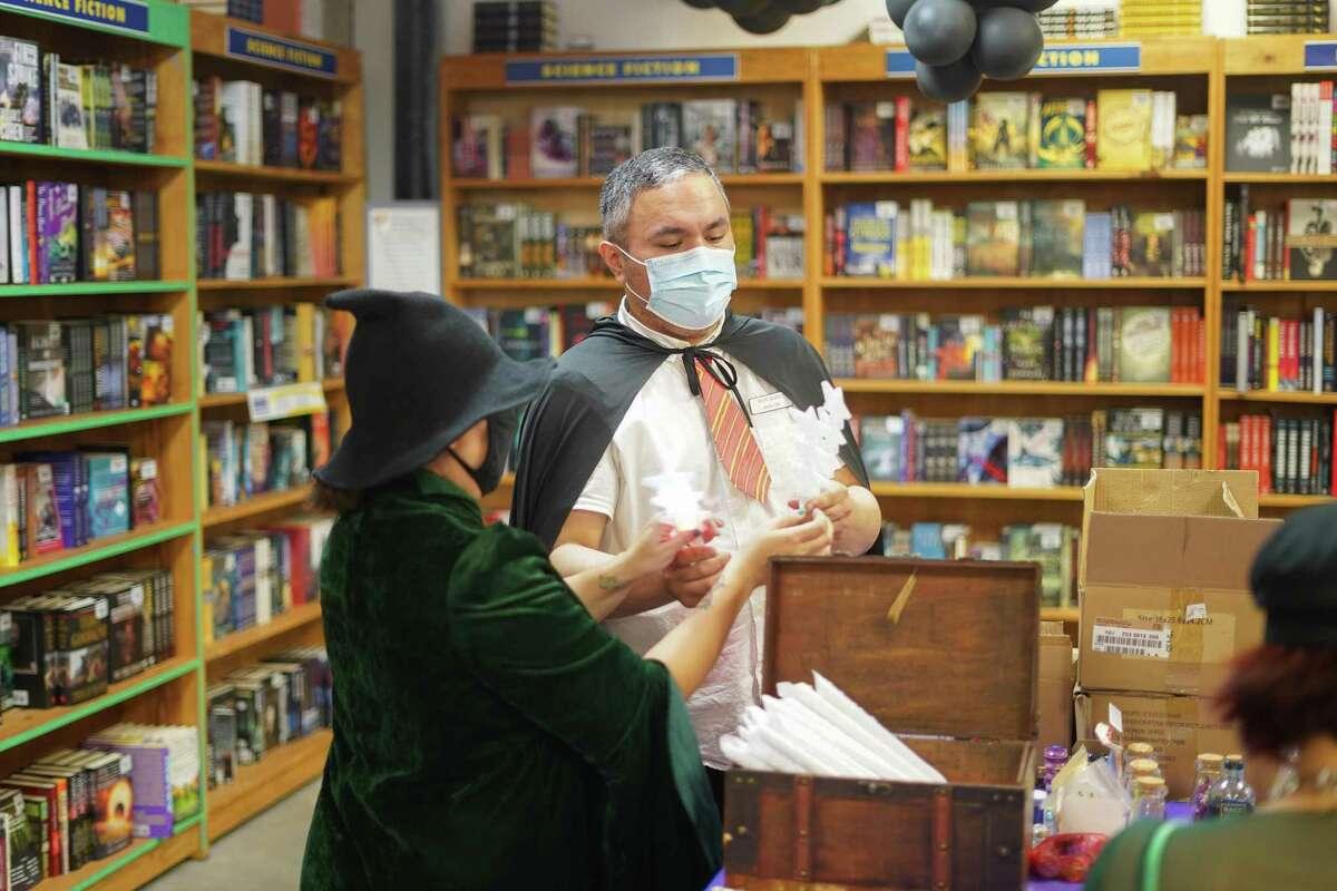 Desde la izquierda, la asistente del gerente de The Book Market, Melissa Pérez y el gerente Jessie Hernández, se preparan para dar varitas mágicas a los asisttentes de Harry Potter Book Night el jueves 24 de junio